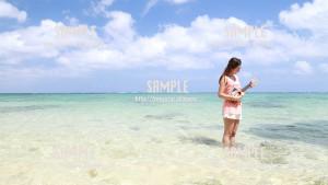 【備瀬】綺麗な海とウクレレを弾く美女 写真素材