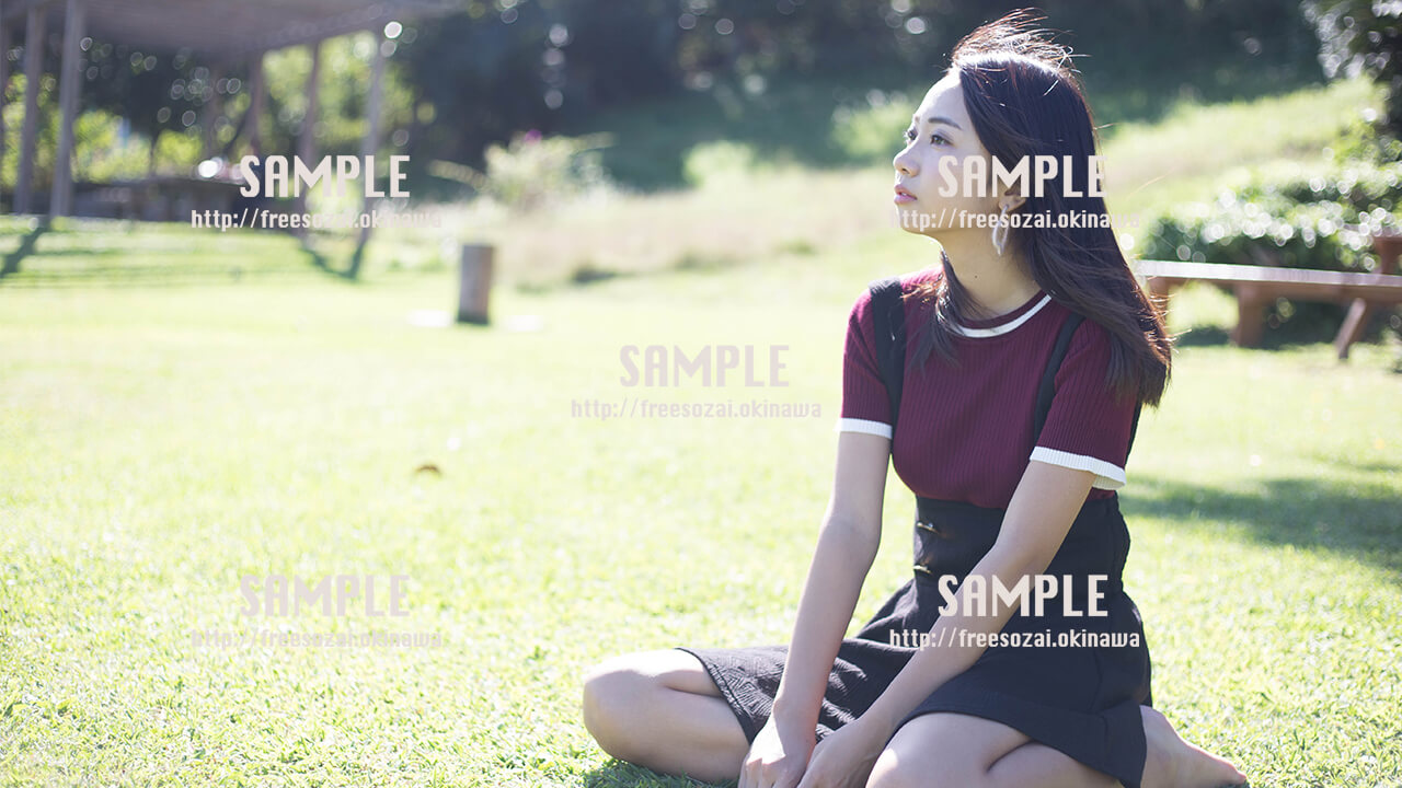 【浦添大公園】ぼーっと芝生に座る美少女 写真素材