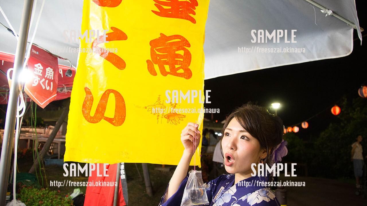 夏祭りで金魚すくいをする女の子の写真