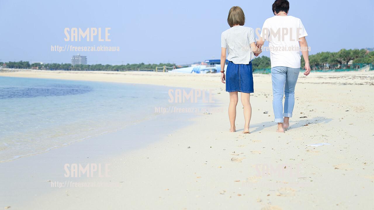 【沖縄】砂浜で手を繋ぐカップル 写真素材