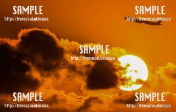 【沖縄】落ちる太陽と上がる飛行機 写真素材